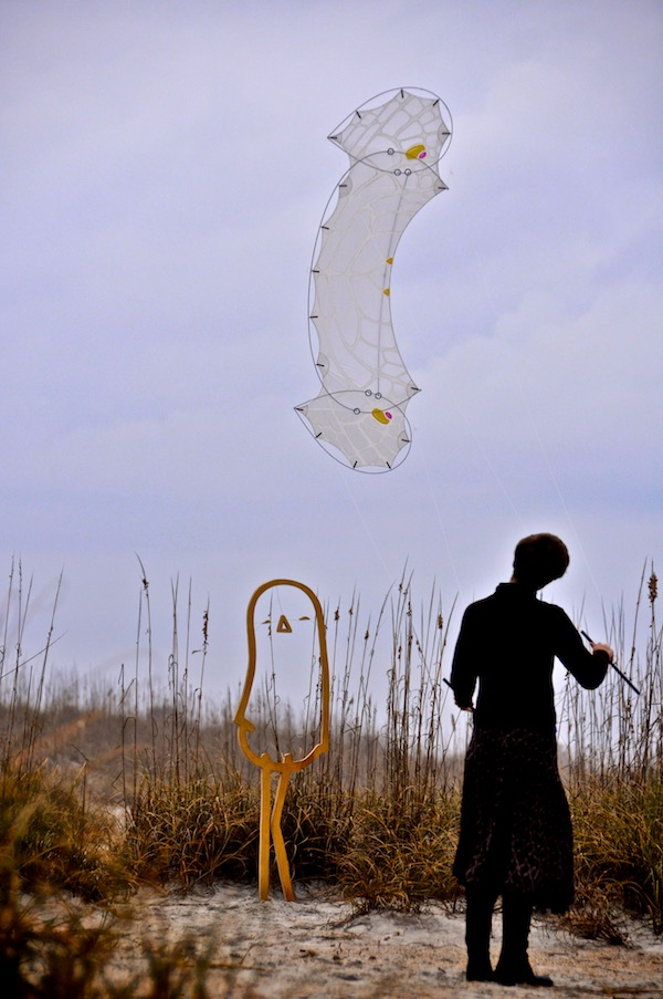 Ruth Whiting flies a kite she painted called a LaceWing Flame designed by Tim Elverston over a wooden cut out of Lonely Bird