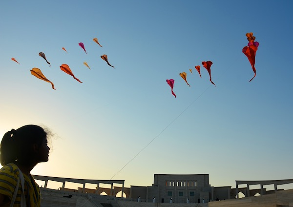 Flowx installation with girl interacting with the kite.  WindFire Designs outdoor event