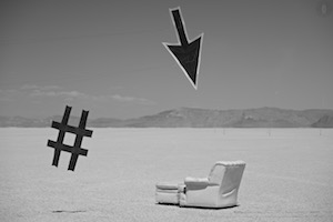 Cursor Kite by Tim Elverston of WindFire Designs - Hashtag kite by Ruth Whiting - seen here in the black rock desert of Nevada, pointing at a leather reclining chair