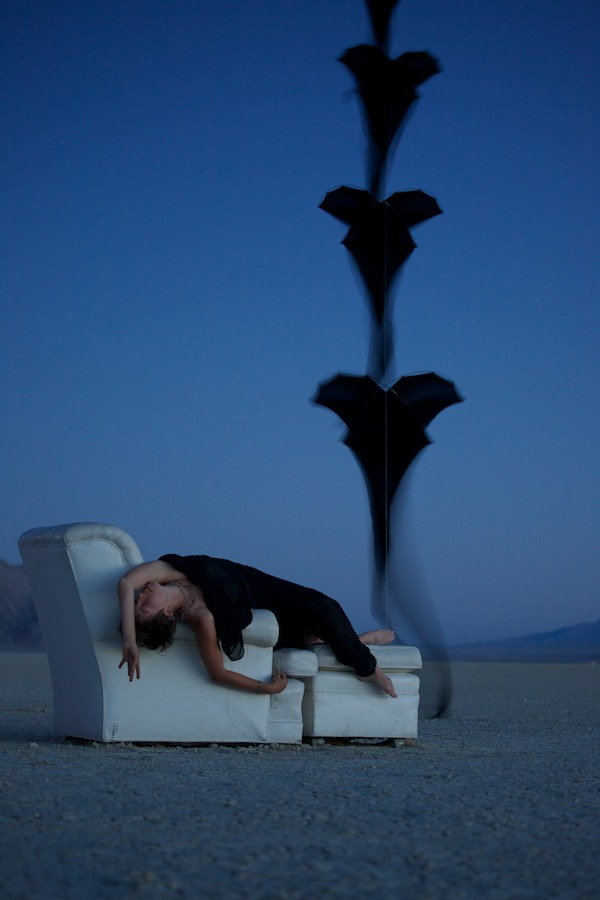 Ruth Whiting reclined in a chair in the Black Rock Desert with a stack of 5 black Flowx silk kites by Tim Elverston