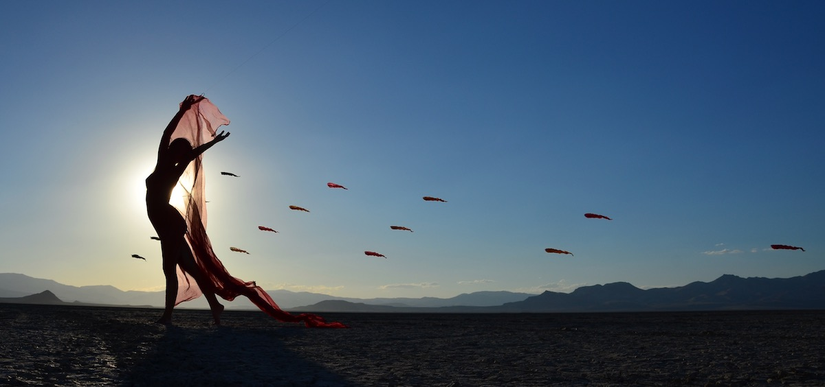 Ruth Whiting in the desert with a triangle installation of Flowx Kites designed by WindFire Designs