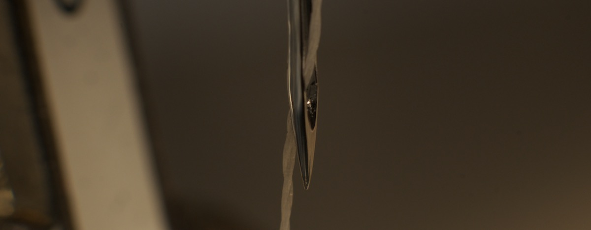 sewing needle showing polyester thread